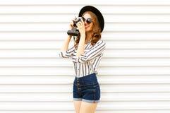 在黑圆的帽子,短裤,在白色墙壁上的白色镶边衬衣的愉快的微笑的年轻女人藏品葡萄酒胶卷相机 免版税库存照片