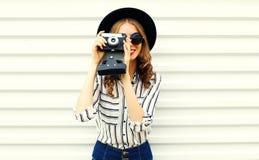 在黑圆的帽子,短裤,在白色墙壁上的白色镶边衬衣的愉快的微笑的年轻女人藏品葡萄酒胶卷相机 图库摄影