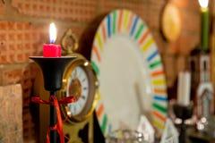 在黑大烛台的燃烧的红色蜡烛栓与红色丝带 在砖壁炉的立场 老减速火箭的时钟和白色板材 免版税库存照片
