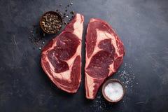 在黑大理石背景的未加工的新使有大理石花纹的肉牛排Ribeye黑色安格斯 发牢骚用在一张黑暗的石桌上的香料 顶视图 免版税库存照片