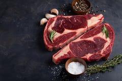 在黑大理石背景的未加工的新使有大理石花纹的肉牛排Ribeye黑色安格斯 发牢骚用在一张黑暗的石桌上的香料 顶视图与 库存照片