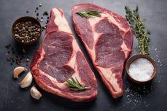 在黑大理石背景的未加工的新使有大理石花纹的肉牛排Ribeye黑色安格斯 发牢骚用在一张黑暗的石桌上的香料 顶视图 免版税图库摄影