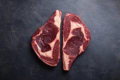 在黑大理石背景的未加工的新使有大理石花纹的肉牛排Ribeye黑色安格斯 发牢骚用在一张黑暗的石桌上的香料 顶视图 图库摄影