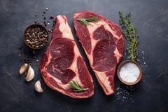 在黑大理石背景的未加工的新使有大理石花纹的肉牛排Ribeye黑色安格斯 发牢骚用在一张黑暗的石桌上的香料 顶层 库存图片