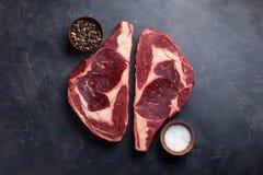 在黑大理石背景的未加工的新使有大理石花纹的肉牛排Ribeye黑色安格斯 发牢骚用在一张黑暗的石桌上的香料 顶视图 免版税库存图片