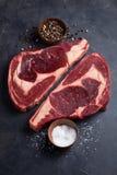 在黑大理石背景的未加工的新使有大理石花纹的肉牛排Ribeye黑色安格斯 发牢骚用在一张黑暗的石桌上的香料 顶视图 库存图片