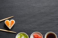 在黑大理石菜单背景的寿司抽象海鲜心脏概念 库存图片