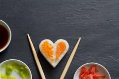 在黑大理石菜单背景的寿司抽象海鲜心脏概念 免版税库存图片