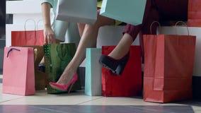 在黑星期五期间,季节性销售,考虑公司的女孩购物入许多袋子在明亮的鞋子的腿附近 股票视频