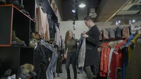 在黑星期五,做购物周末和女朋友的滑稽的夫妇给她男朋友许多衣裳为她举行- 股票视频