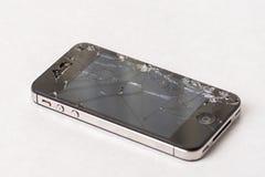 在黑智能手机的被碰撞的显示在白色大理石背景上 库存照片