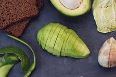 在黑暗的切板的切的成熟鲕梨 素食主义者和健康食品概念 免版税库存图片