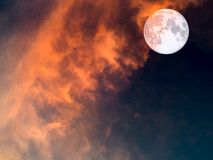 在黑暗的天空和红色软的云彩的超级月亮 免版税库存照片