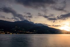 在黑暗的山湖的温暖的日落 图库摄影