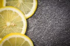 在黑暗的新成熟柠檬切片地方的柠檬石背景柑桔顶视图的 库存图片