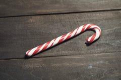 在黑暗的木板条背景的红色和白色棒棒糖  关闭 婴孩圣诞节克劳斯帽子演奏s圣诞老人的母亲照片一起佩带 免版税库存图片