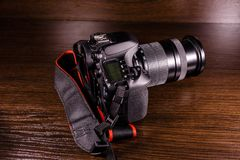 在黑暗的木桌上的现代dslr照相机 图库摄影