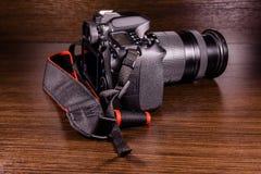 在黑暗的木桌上的现代dslr照相机 免版税库存图片