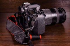 在黑暗的木桌上的现代dslr照相机 库存图片