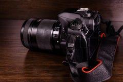 在黑暗的木桌上的现代dslr照相机 免版税库存照片