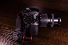 在黑暗的木桌上的现代dslr照相机 库存照片