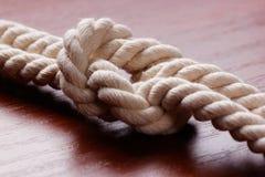 在黑暗的木桌上的白色绳索结 cpose yp概念 库存照片