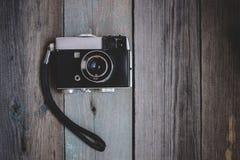 在黑暗的木桌上的葡萄酒照相机 免版税库存照片