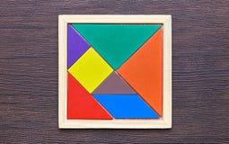 在黑暗的木背景的一个七巧板难题 免版税库存照片
