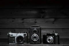 在黑暗的木背景的三台影片照相机 免版税图库摄影
