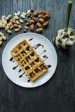 在黑暗的木背景的巧克力盖的传统比利时华夫饼干 鲜美早餐 用raschlichnymi坚果装饰 库存照片