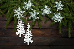在黑暗的木背景的绿色生存云杉的分支 与锥体和白色雪花和纸板基督的新年背景 图库摄影