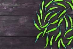 在黑暗的木背景的绿色辣椒 库存照片