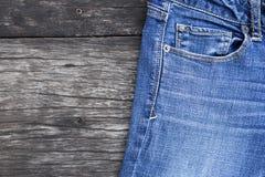 在黑暗的木背景的蓝色牛仔裤 免版税库存图片