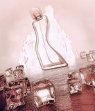 在黑暗的木背景的香水瓶与反射 射击a 免版税库存照片