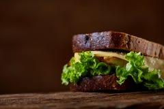在黑暗的木背景的鲜美和新鲜的三明治,特写镜头 免版税库存照片