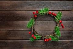 在黑暗的板条木头背景的传统手工制造圣诞节花圈绿色杉树分支枝杈霍莉莓果 顶视图 库存照片