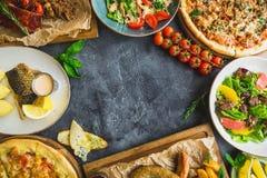 在黑暗的桌上的鲜美盘 烤猪排、薄饼、沙拉、鱼和香肠用油煎的土豆 平的位置 顶视图 食物fram 库存图片
