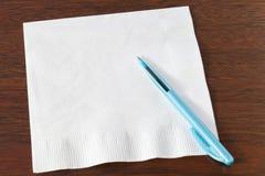 在黑暗的橡木的餐巾和绿松石圆珠笔 免版税库存照片