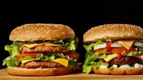 在黑暗的灰色极谱背景隔绝的木桌上的两个工艺牛肉汉堡 影视素材