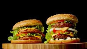 在黑暗的灰色极谱背景隔绝的木桌上的两个工艺牛肉汉堡 股票录像