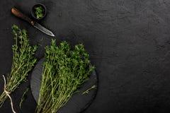 在黑暗的石背景的新鲜的草本麝香草 健康食品,烹调,干净吃,顶视图,平的位置,拷贝空间 免版税库存图片