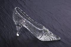 在黑暗的石背景的水晶灰姑娘鞋子 免版税库存图片