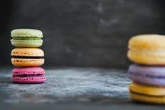 在黑暗的石背景的被分类的五颜六色的法国蛋白杏仁饼干 免版税图库摄影