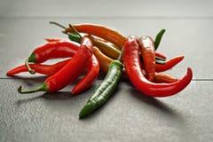 在黑暗的织地不很细背景的五颜六色的辣椒 库存图片