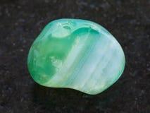 在黑暗的翻滚的绿色被洗染的玛瑙宝石 库存照片