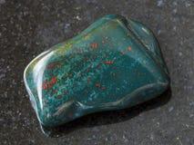 在黑暗的翻滚的绿色鸡血石的宝石 免版税库存照片
