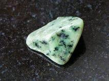 在黑暗的翻滚的绿色Grossular宝石 免版税库存图片