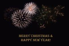 在黑暗的背景和文本`圣诞快乐&新年好`的烟花 库存图片