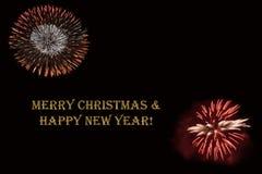 在黑暗的背景和文本`圣诞快乐&新年好`的烟花 免版税库存照片