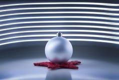 在黑暗的背景的一个唯一银色圣诞树球与光线影响 库存照片